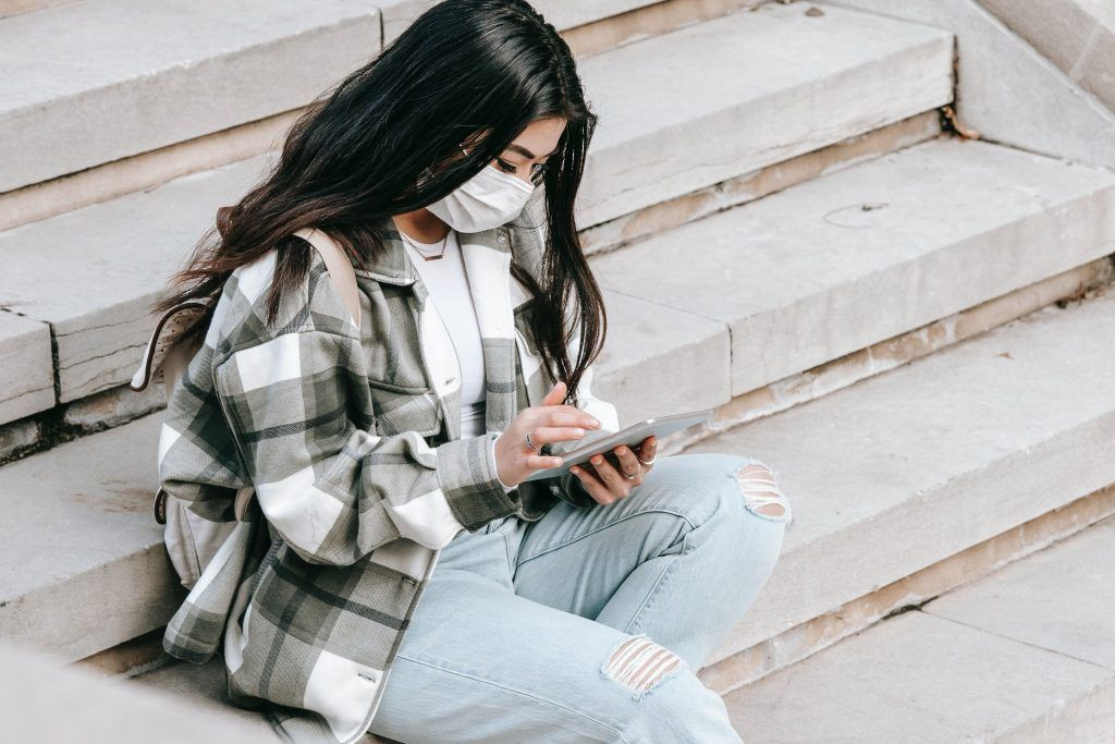 Chica con mascarilla mirando el móvil. Infodemia, pandemia digital por infoxicación.